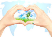 Human hand and nature on world map background. — Stock Photo