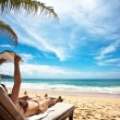 Relaxing and reading at the beach — Stockfoto
