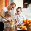 Mother with children squeezed orange juice — Stock Photo #4715230