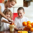 Mother with children squeezed orange juice — Stock Photo #4715235