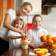 Mother with children squeezed orange juice — Stock Photo #4715237