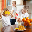 Mother with children squeezed orange juice — Stock Photo #4715243