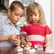 Children are considering a magnifying glass collection of stones - Foto de Stock