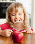 Child are considering a magnifying glass apple — Stock Photo