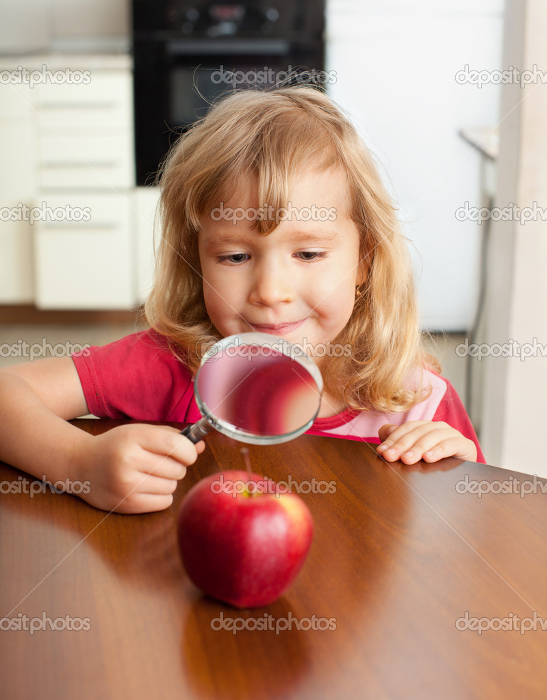 Child are considering a magnifying glass apple  Stock Photo #5163966