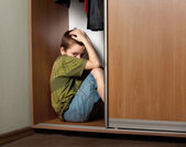 Sad boy, hiding in the closet — Stock Photo
