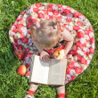Girl eating an apple and looking book on the grass — Stock Photo