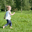Girl runs around the green grass in the park — Stock Photo