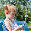 Thoughtful girl with a dandelion on a park bench — Stock Photo