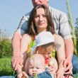A happy family on the lawn, against the sky — Stock Photo