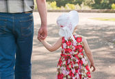 Girl in white hat and dress goes with his father's hand — Stock Photo