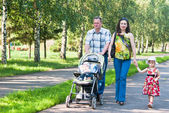 Happy family walks in the park — Stock Photo