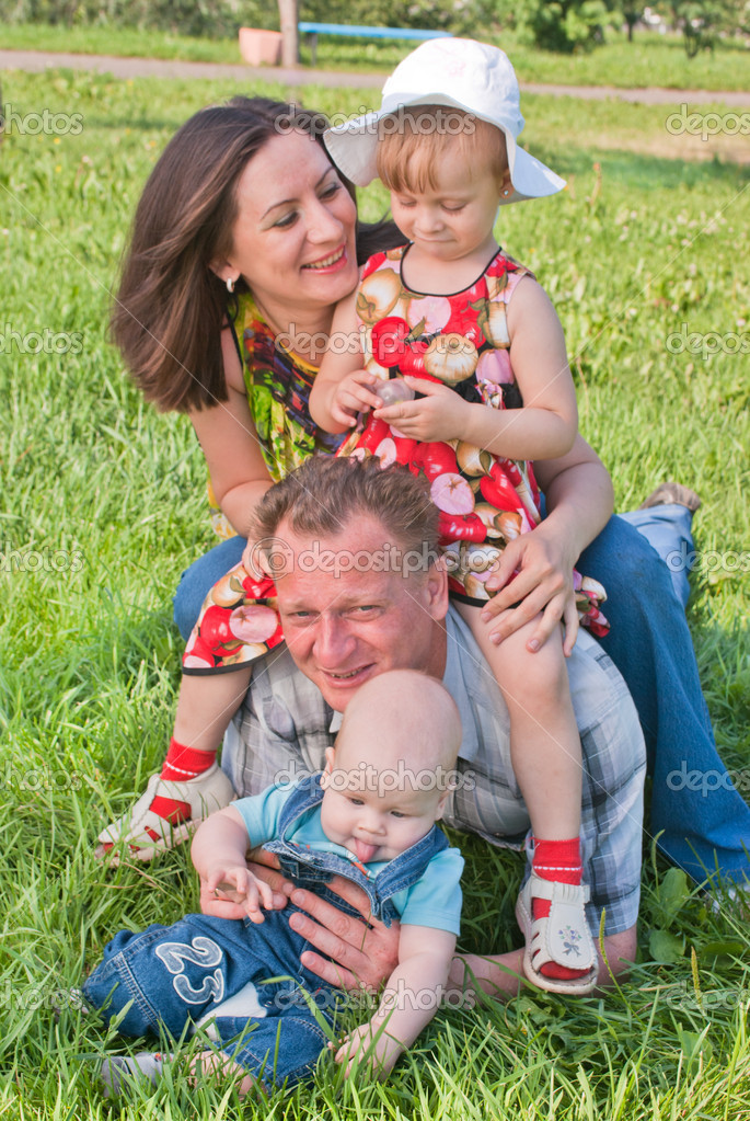 A happy family of four on the lawn — Stock Photo #4146704