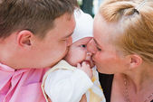 Mother and father kissing baby's cheek — Stock Photo