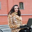 Brunette with laptop outdoors - Stock Photo