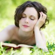Young woman reading outdoors - Stok fotoğraf