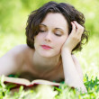 Young woman reading outdoors - Stockfoto