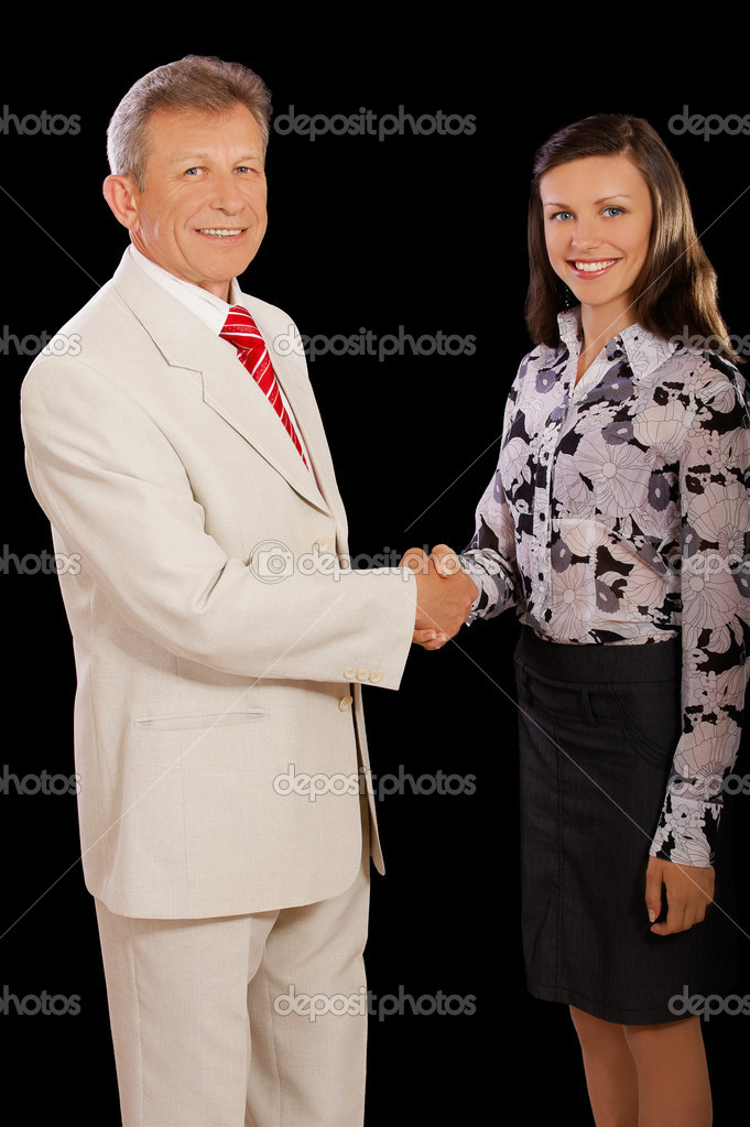 Portrait of senior businessman and young woman secretary shaking hands on black  — Stock Photo #4016149