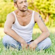 Young man sits on grass — Foto Stock