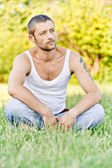 Young man sits on grass — Stockfoto