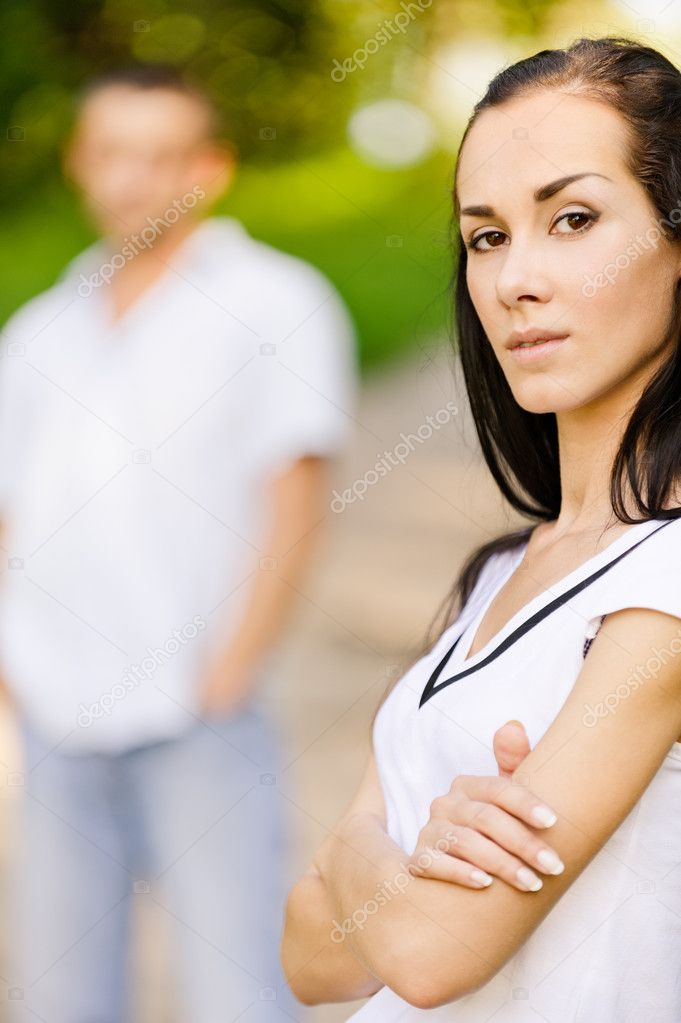 Young beautiful woman in foreground in summer solar park. Man stands behind in the distance. — Stock Photo #4054330