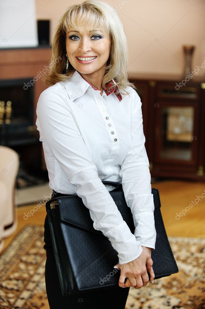 Portrait of beautiful smiling mature business woman in white shirt with black portfolio in hands, against magnificent interior. — Stock Photo #4059493