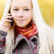 Young blonde talks on cellular telephone - Stock Photo
