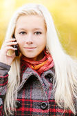 Young blonde talks on cellular telephone — Stock Photo