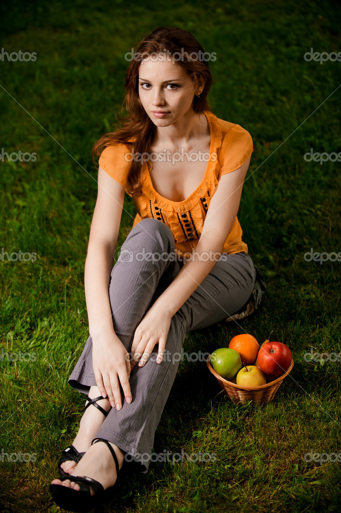Beautiful girl in orange blouse sits on green grass. Basket with ripe apples stands about it. — Stock Photo #4170308