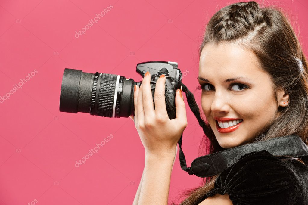 Young beautiful smiling woman-photographer hold in hands DSLR, going to make picture, on red background.  Stock Photo #4189843