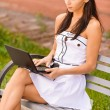 Young beautiful brunette with black laptop. — Stock Photo