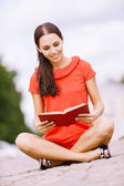 Lovely young woman reads book — Stock Photo