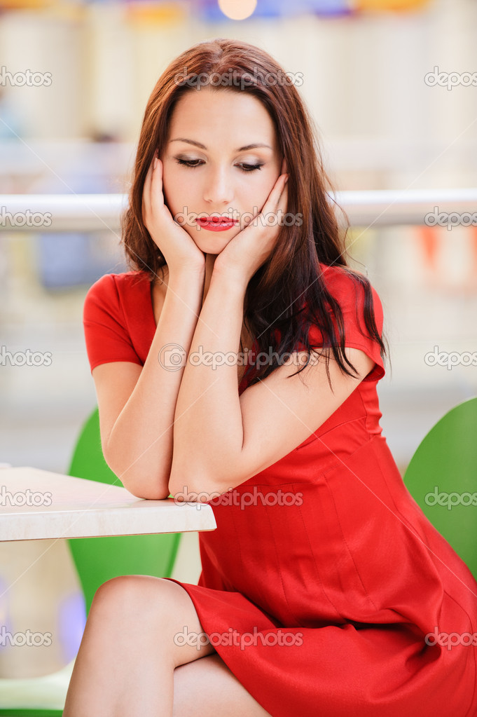 Young beautiful dark-haired woman in red dress sits at little table in small cafe and thinks of unfortunate life.  Stock Photo #4199061