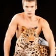 Young man and spotty leopard - Stock fotografie