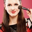 Woman applying blusher - Stock Photo