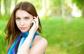 Beautiful woman talks by mobile phone — Stock Photo