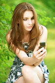 Beautiful young woman with mobile phone — Stock Photo