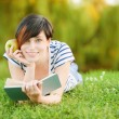 Girl lying on the grass and reading a book - Stock Photo