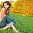 Woman sits on green grass — Stock Photo