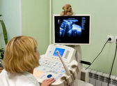 Obstetrician examining pregnant belly by ultrasonic scan. — Stock Photo