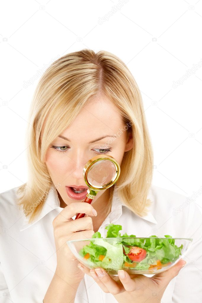 The surprised woman considers through a magnifier the vegetables, isolated — Stock Photo #3986061