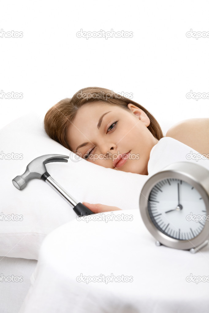 The girl lies in bed and is going to break a hammer an alarm clock — Stock Photo #3986197