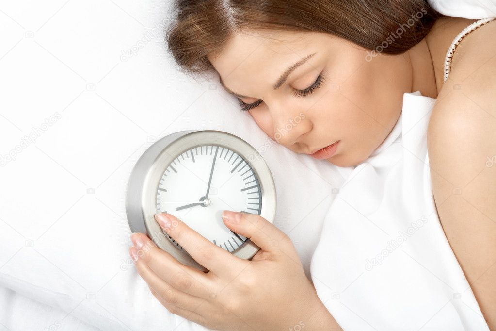 The young woman lies in bed with an alarm clock in hands — Stock Photo #3986501
