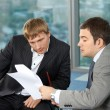 Two business men at office talk about the document content — Stock Photo #3991789