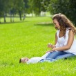 Happy mum with son on a lawn in park — Stock Photo #3997587