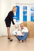 The woman allows to the man to sign papers in new apartment — Stock Photo