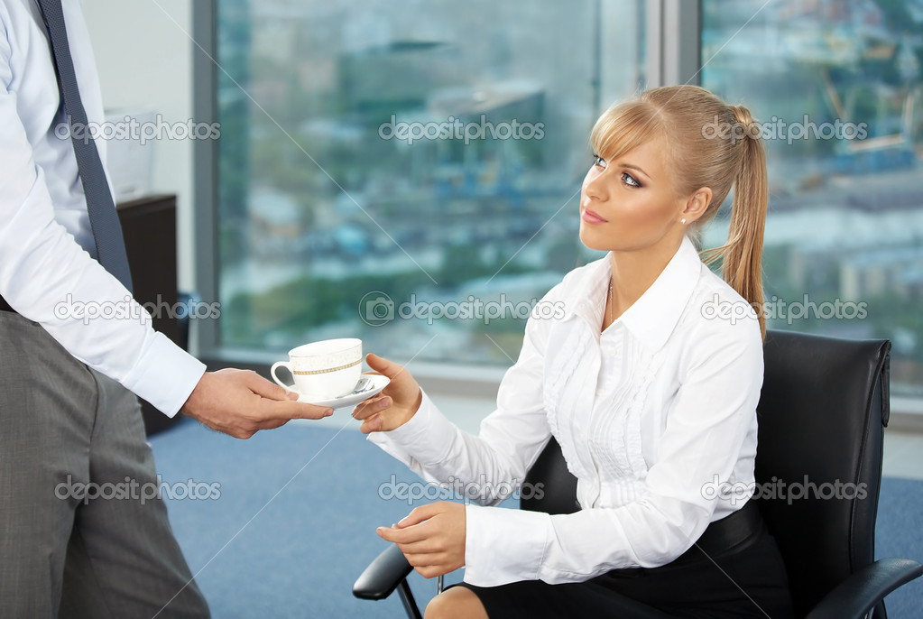 The beautiful business woman at office accepts a cup of coffee from the colleague  Stock Photo #3991793