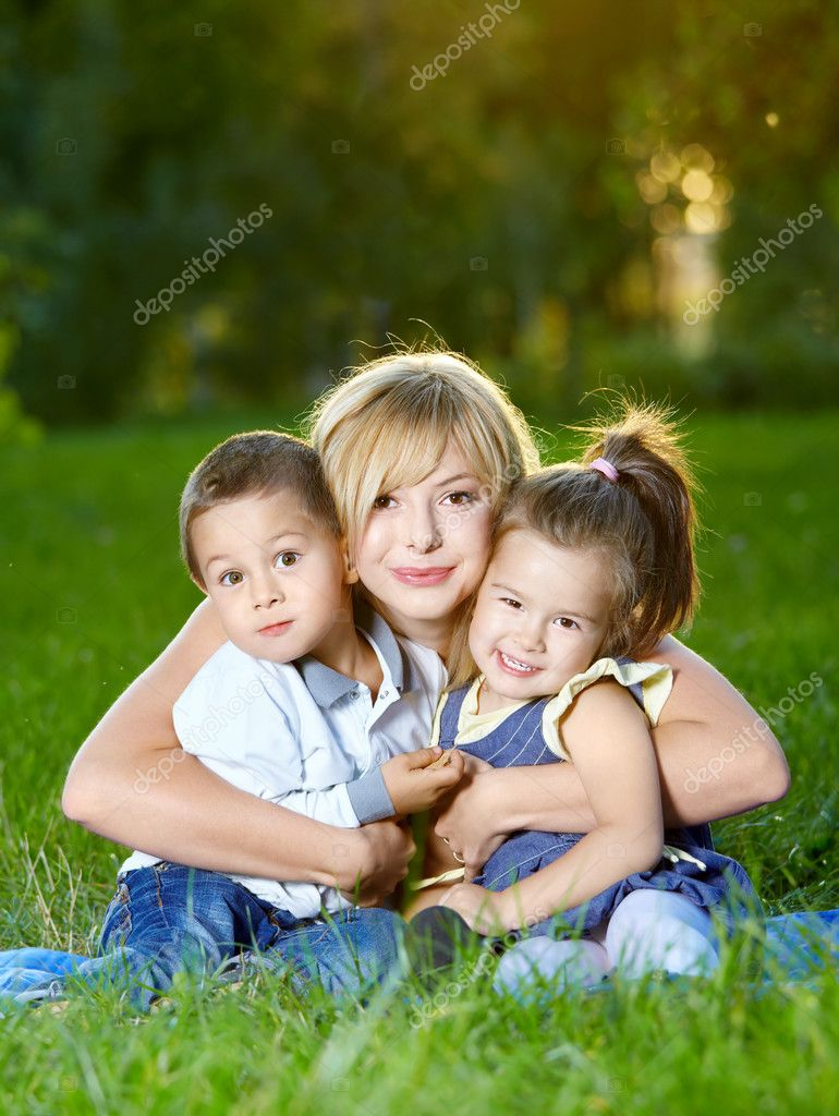 Mother embraces two children on a summer lawn — Stock Photo #4014320