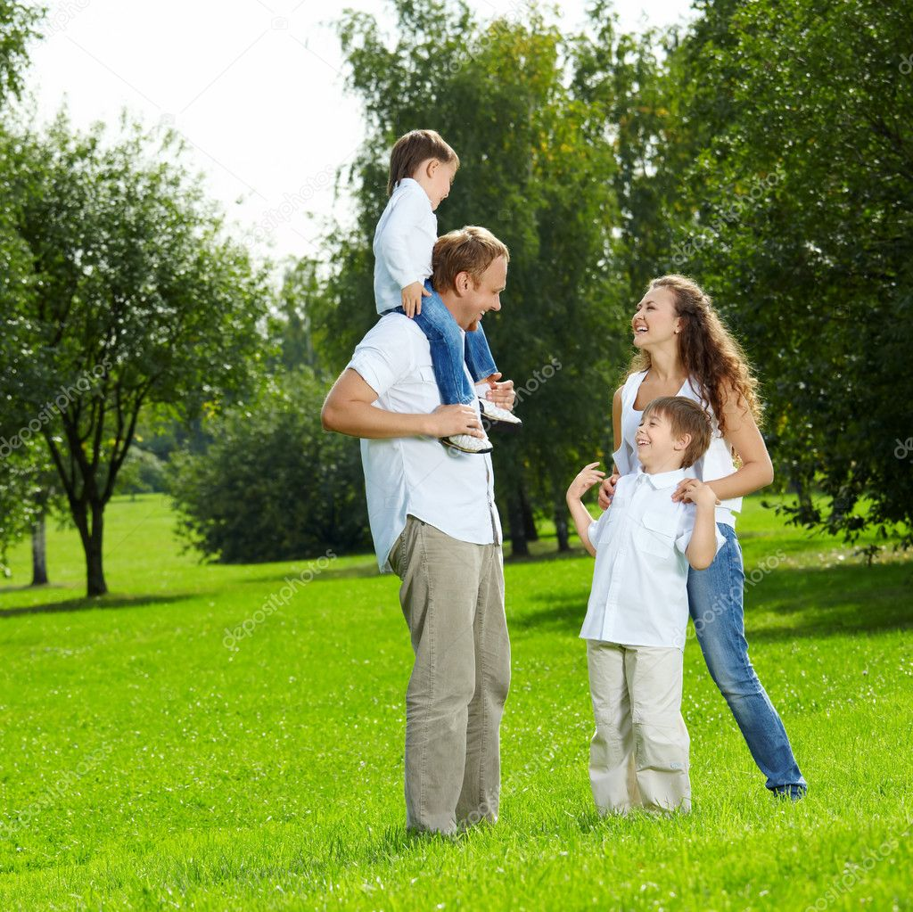 Laughing family with two sons walks in a summer garden — Stock Photo #4014723