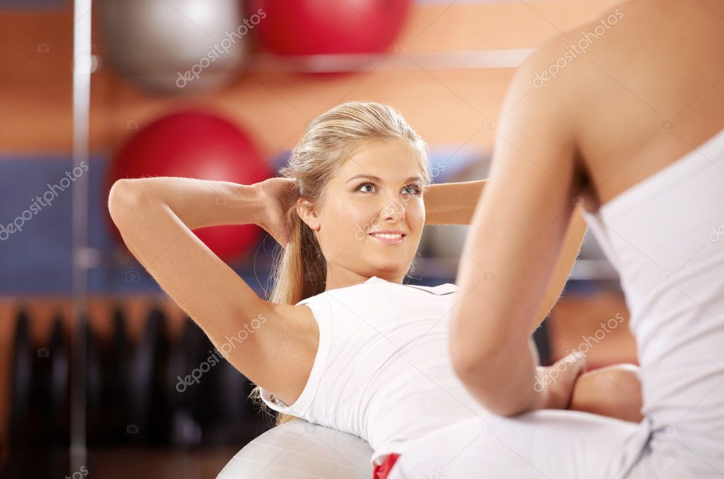 The girl does twisting on fitball with support of the trainer — Stock Photo #4016220